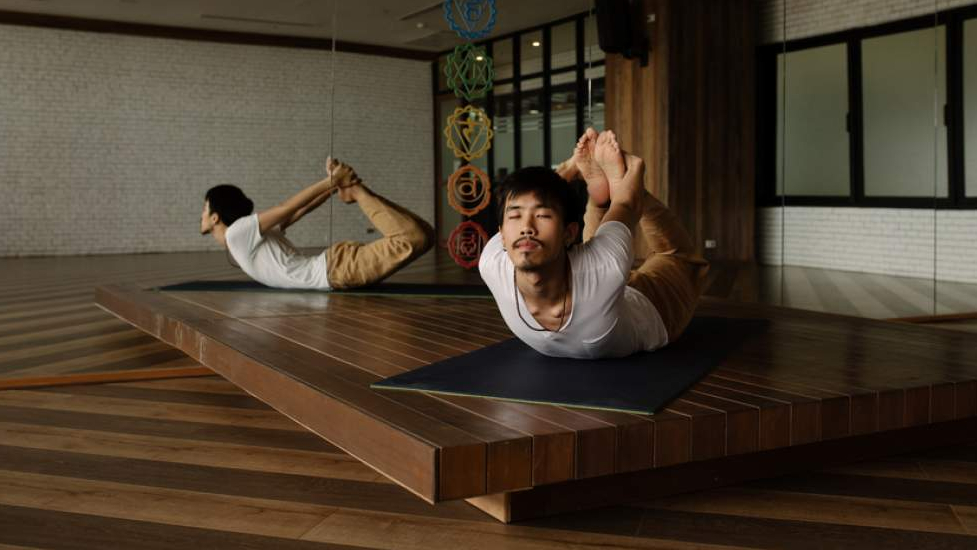 Asian Man Practicing Yoga Alone In Studio