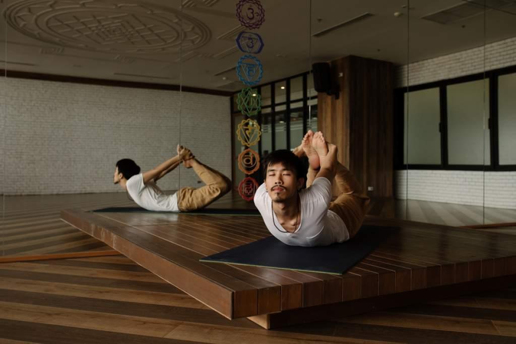 Asian Man Practicing Yoga Alone In Studio