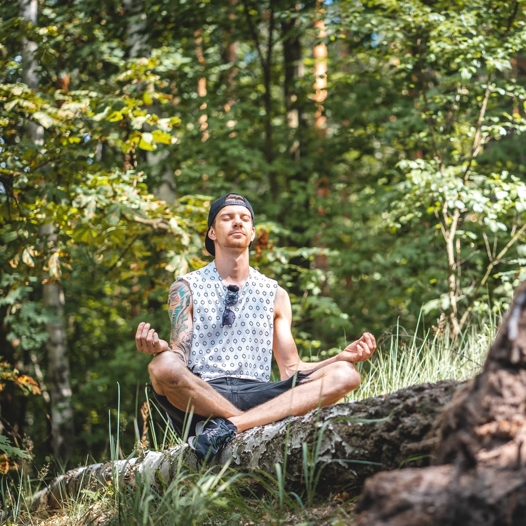 Man Sitting In Yoga Pose In Nature