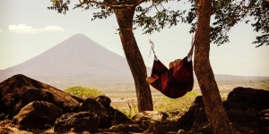 Person Relaxing In Hammock Near Mountain