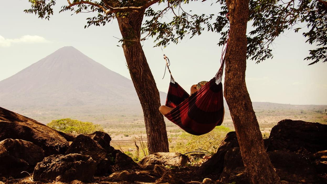 Person Relaxing In Hammock Near Mountain