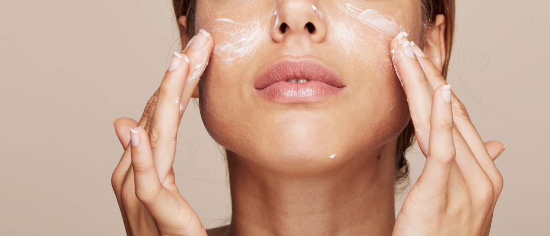Closeup of Woman Applying Cream to Her Face