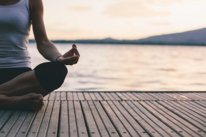 Woman Sitting In Yoga Pose Near Water