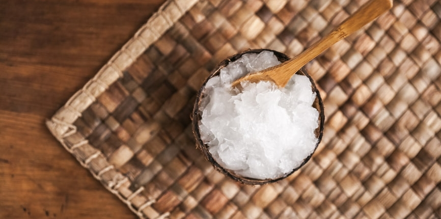 Small bowl of solidified coconut oil on place mat