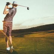 Man golfing at sunrise
