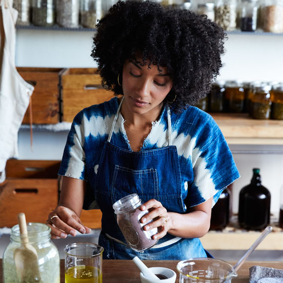 African American Woman Mixing Ingredients In Her Studio