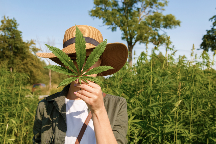 woman-in-hat-demonstrating-leaf-of-cannabis