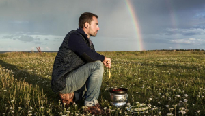 Man with Wooden Spoon and Pot on Meadow with Rainbow