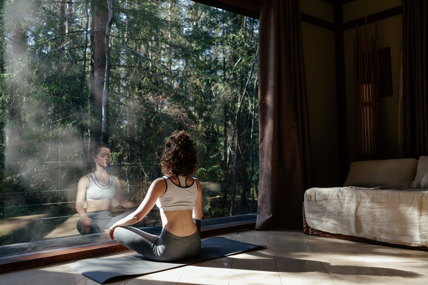Woman sitting in lotus position in front of panoramic window