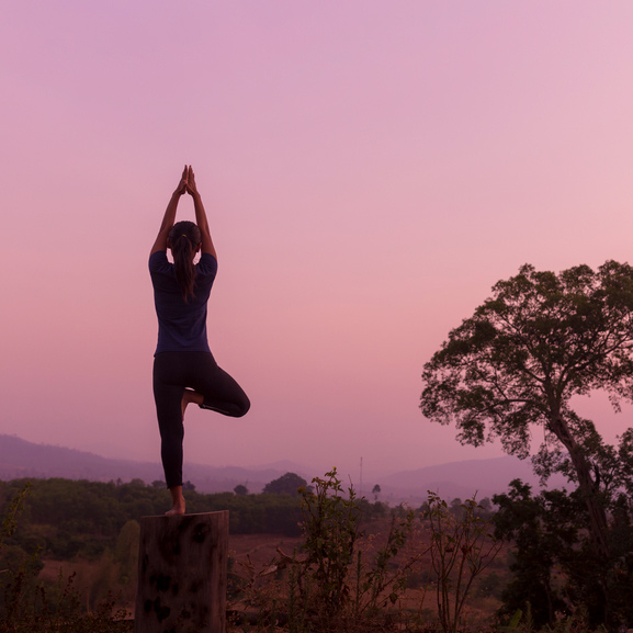 Woman Practicing Yoga At Sunrise In Nature