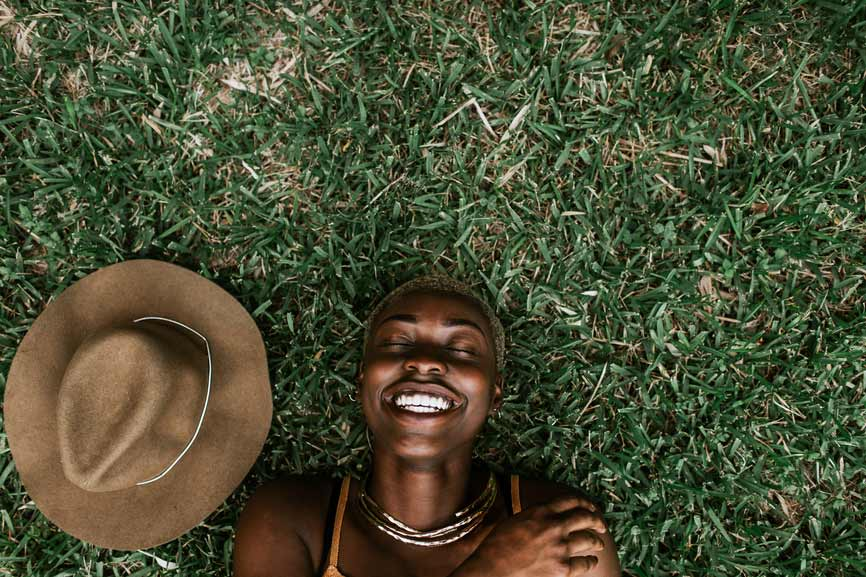 Black Woman With Hat Laying On Grass Smiling