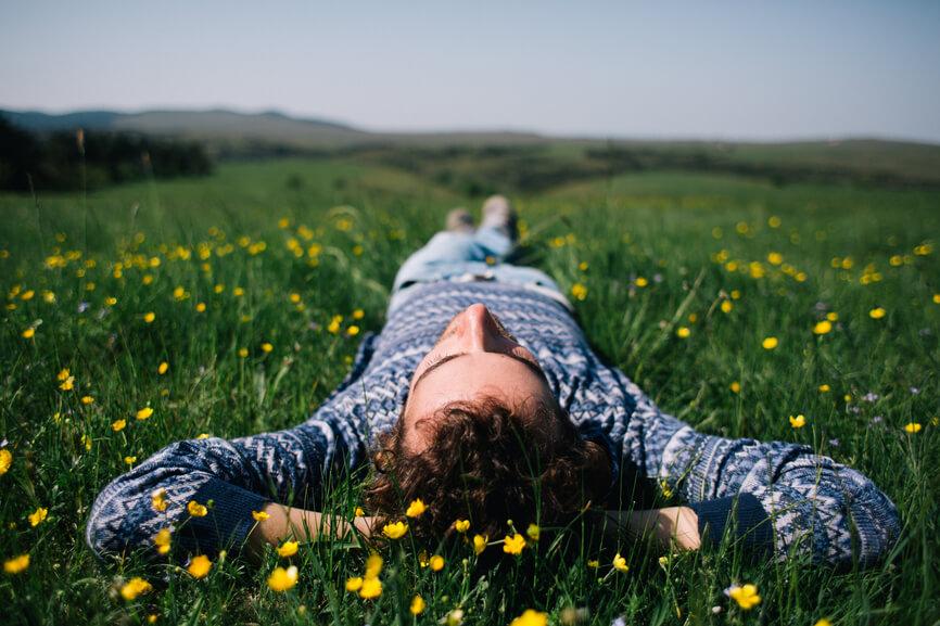 Man Laying On Grass Field