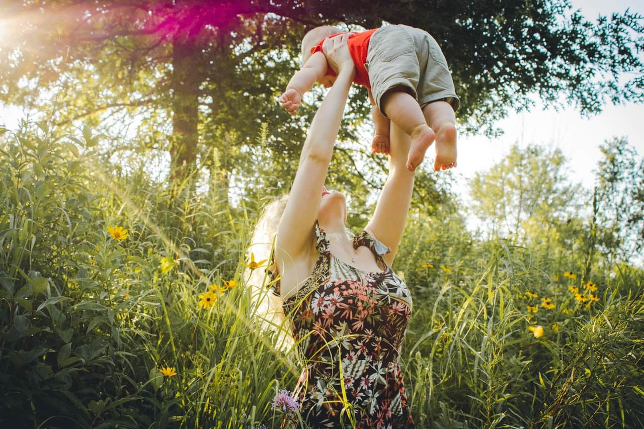 Woman carrying baby near grass