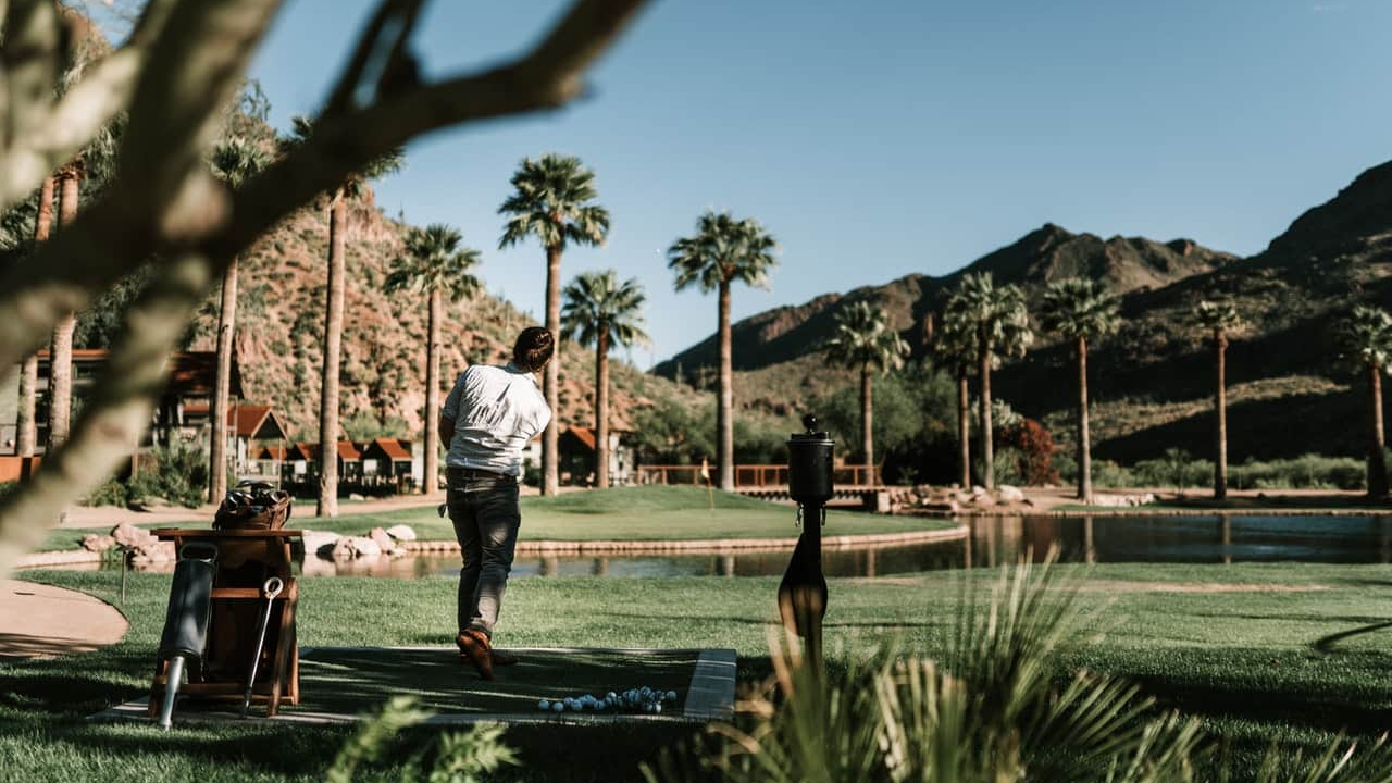 Photo of man golfing on grass field