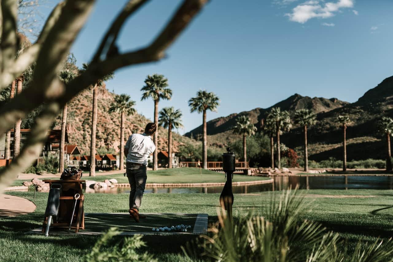 Photo of man golfing on grass field