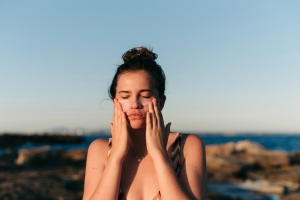 Woman At Beach Applying Lotion To Face