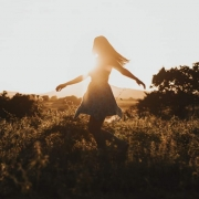 Woman Dancing On Field At Sunset