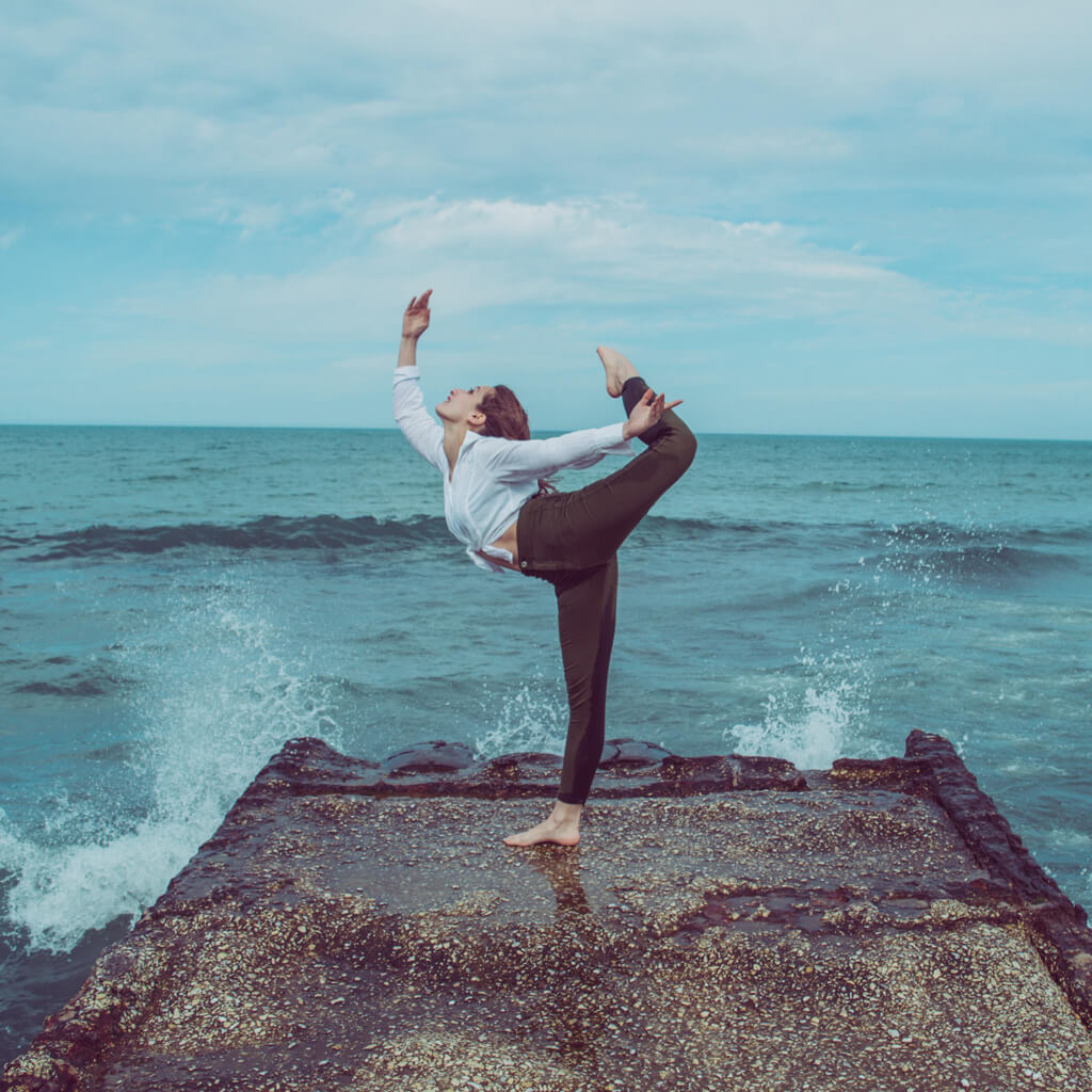 Woman Holding Ballet Pose Near Ocean