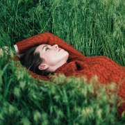Woman Relaxing In Green Grass Field