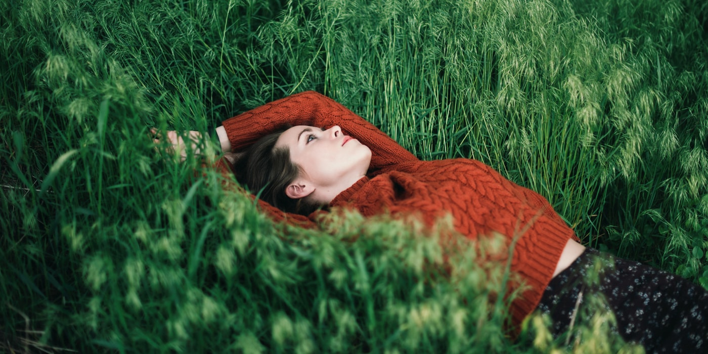 Woman Relaxing In Green Grass Field