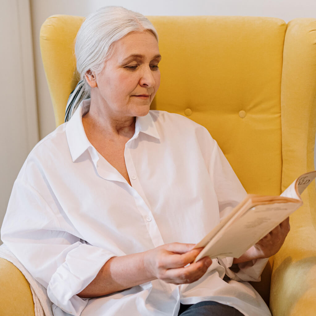 Woman Sitting In Armchair Reading Book