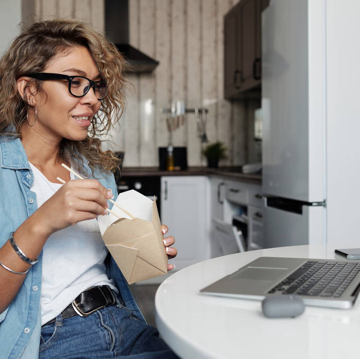 This lady has the right idea. She's got some takeout, and she's got a streaming service loaded on her laptop that allows her to watch her favorites anywhere. She's living her best life, almost certainly.