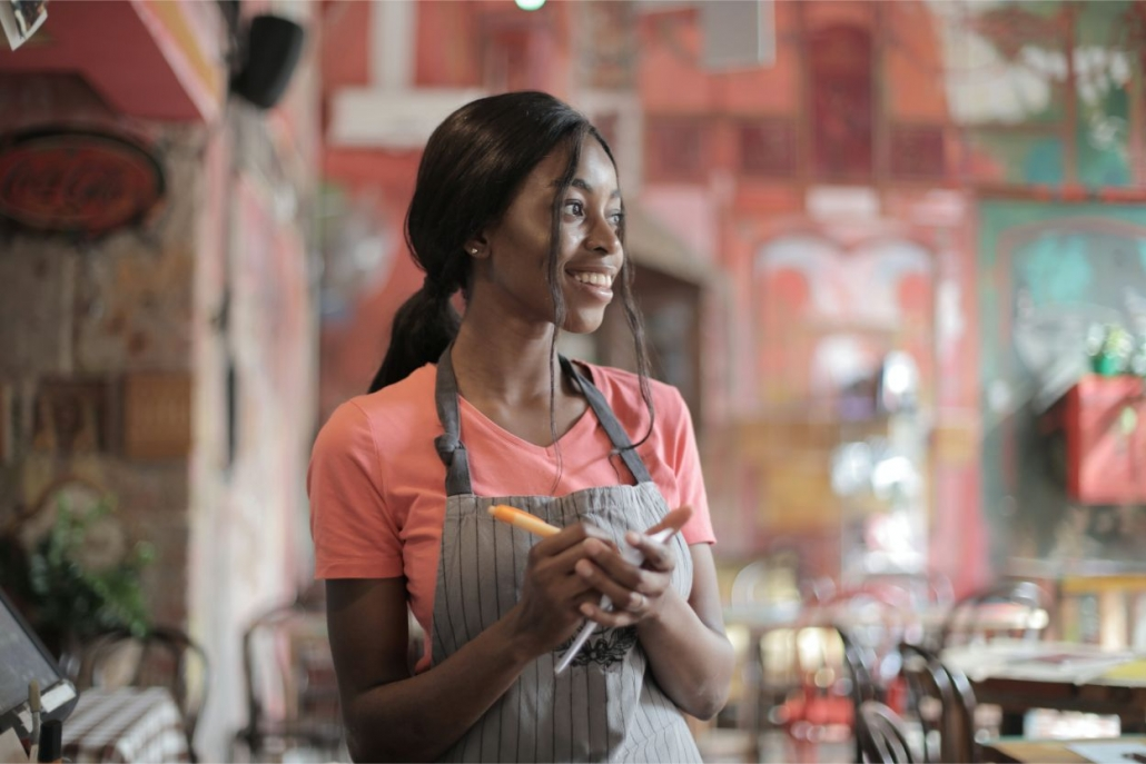 Young Waitress Smiling While Taking Order