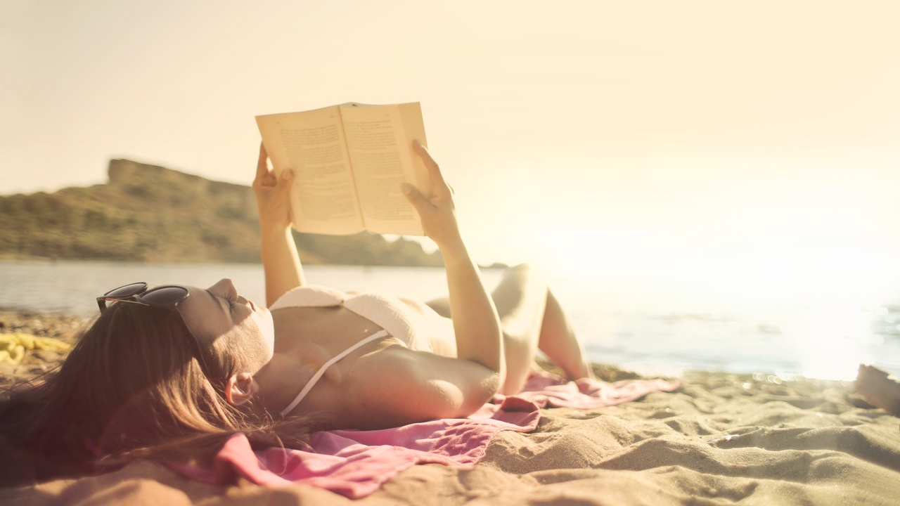 woman-lying-on-beach-reading-book