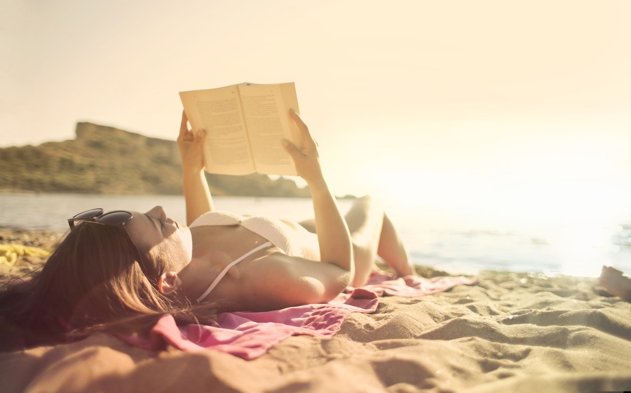 woman-lying-on-beach-reading-book