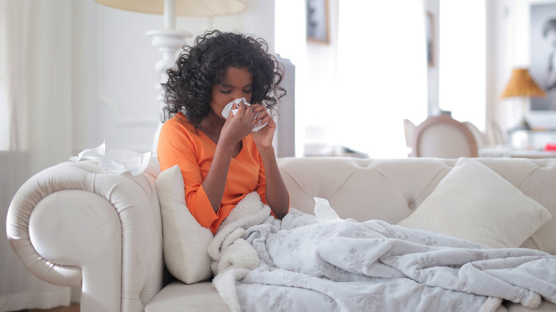 Woman blowing nose on couch