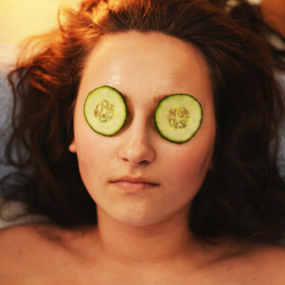 Woman with DIY Facial cucumbers on eyes