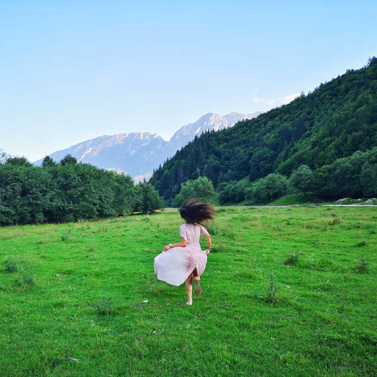Woman running barefoot in grassy mountain meadow