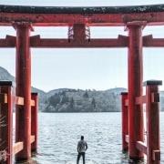 Man standing under Japanese gate next to lake