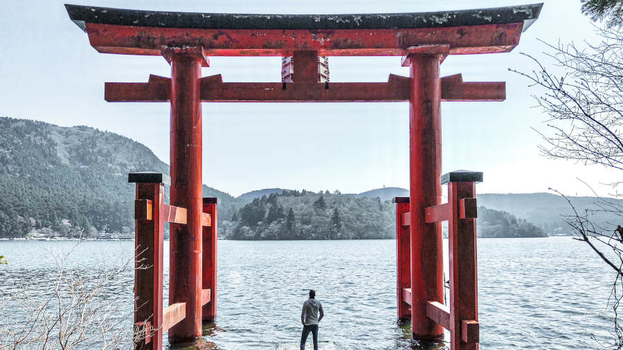 Man standing under Japanese gate next to lake