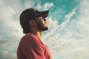 man-wearing-black-cap-with-eyes-closed-under-cloudy-sky