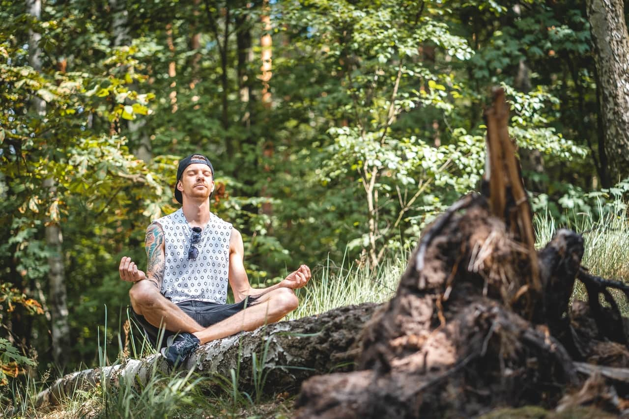 man-meditating-on-a-tree-log