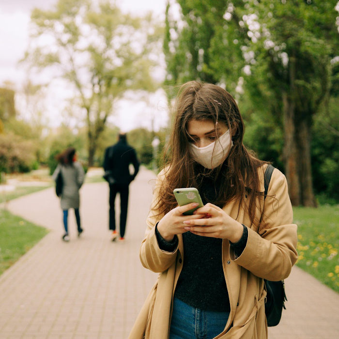 Woman wearing mask looks at cell phone