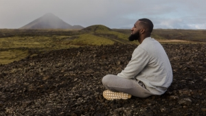 Man sitting on rocks under cloudy sky