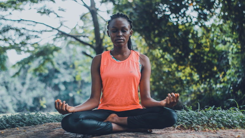 Woman meditating on the complexities of CBD oil products. CBD oil topicals from Synchronicity Hemp Oil seemed the best fit for her.