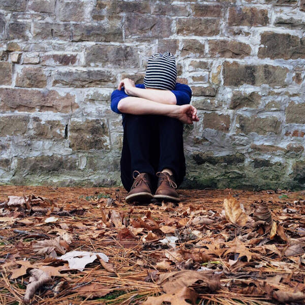 Person covering face and looking depressed, sitting on leaves in front of brick wall