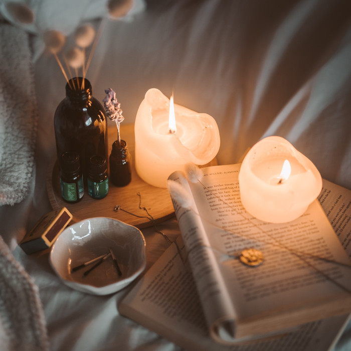 Candles on a book with tinctures nearby